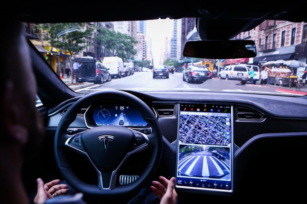 "A driver rides hands-free in a Tesla Model S equipped with Autopilot hardware and software in New York on Sept. 19. California says a true autonomous vehicle is one that is ""equipped with technology that has the capability of operating or driving the vehicle without the active physical control or monitoring of a natural person."" (Christopher Goodney/Bloomberg News)"